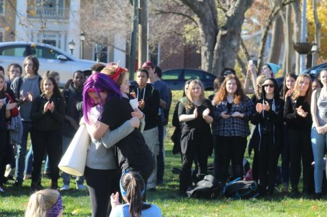 Abigail Morris (right) hugs another ARHS student, surrounded by walkout participants. (Caeli Chesin/Amherst Wire)