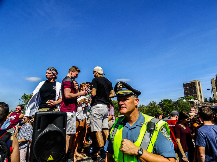 A+police+officer+stands+in+front+on+students+during+a+UMass+Amherst+football+tailgate+in+2016.