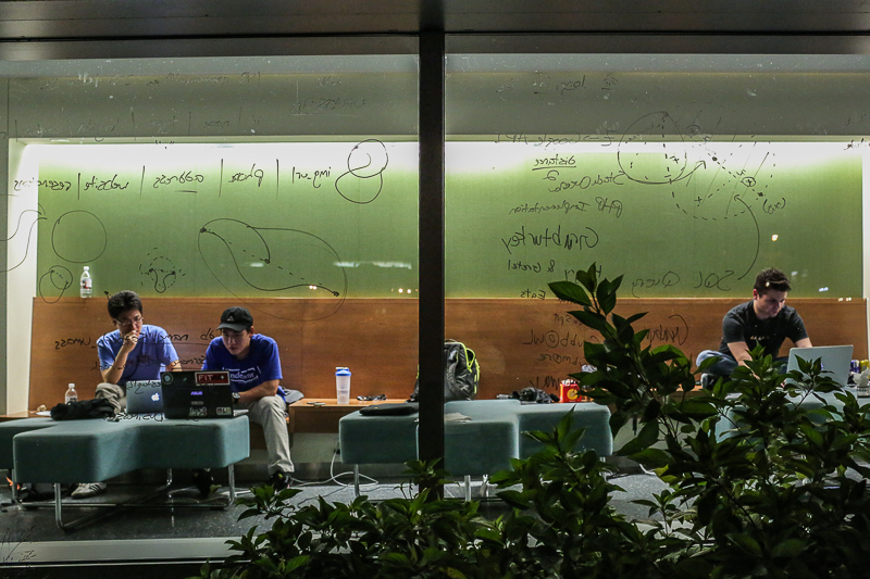 From left: Chris Chiang, Dan Wu, and Sazan Dauto are framed by their notes as they work on their app late into Saturday night at the fourth annual HackUMass on Oct. 8, 2016.