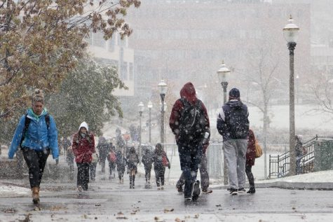 Students, all bundled up, head to class in the snow.