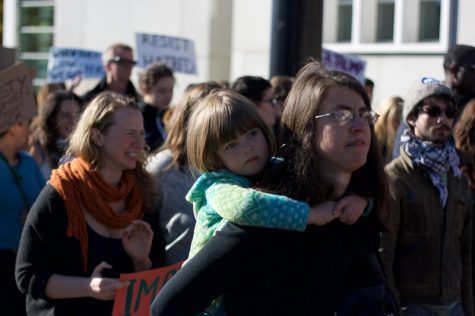 Jennifer Atlee marches with her daughter on her back at the anti-Trump protest in Springfield on Sunday, Nov. 13, 2016. While other protesters felt joy in coming together, Atlee was brought to tears by what a Trump presidency means to her and her daughter. (Morgan Hughes/Amherst Wire)