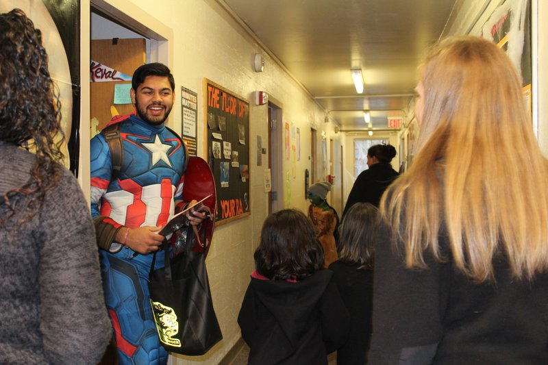 Keval Kapadia, senior legal studies major and fourth year candy-giver welcomes Amherst community members at the entrance of his Crabtree dorm room. (Caeli Chesin/Amherst Wire)