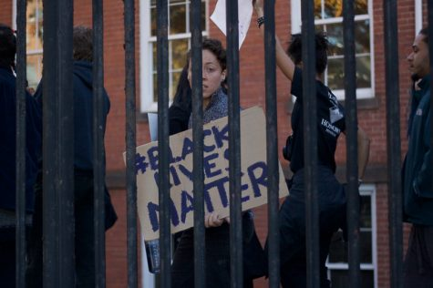 "A protesters holds a ""#BlackLivesMatter"" sign as they march behind a fence at the edge of downtown Springfield on Sunday, Nov. 13, 2016. (Morgan Hughes/Amherst Wire)"