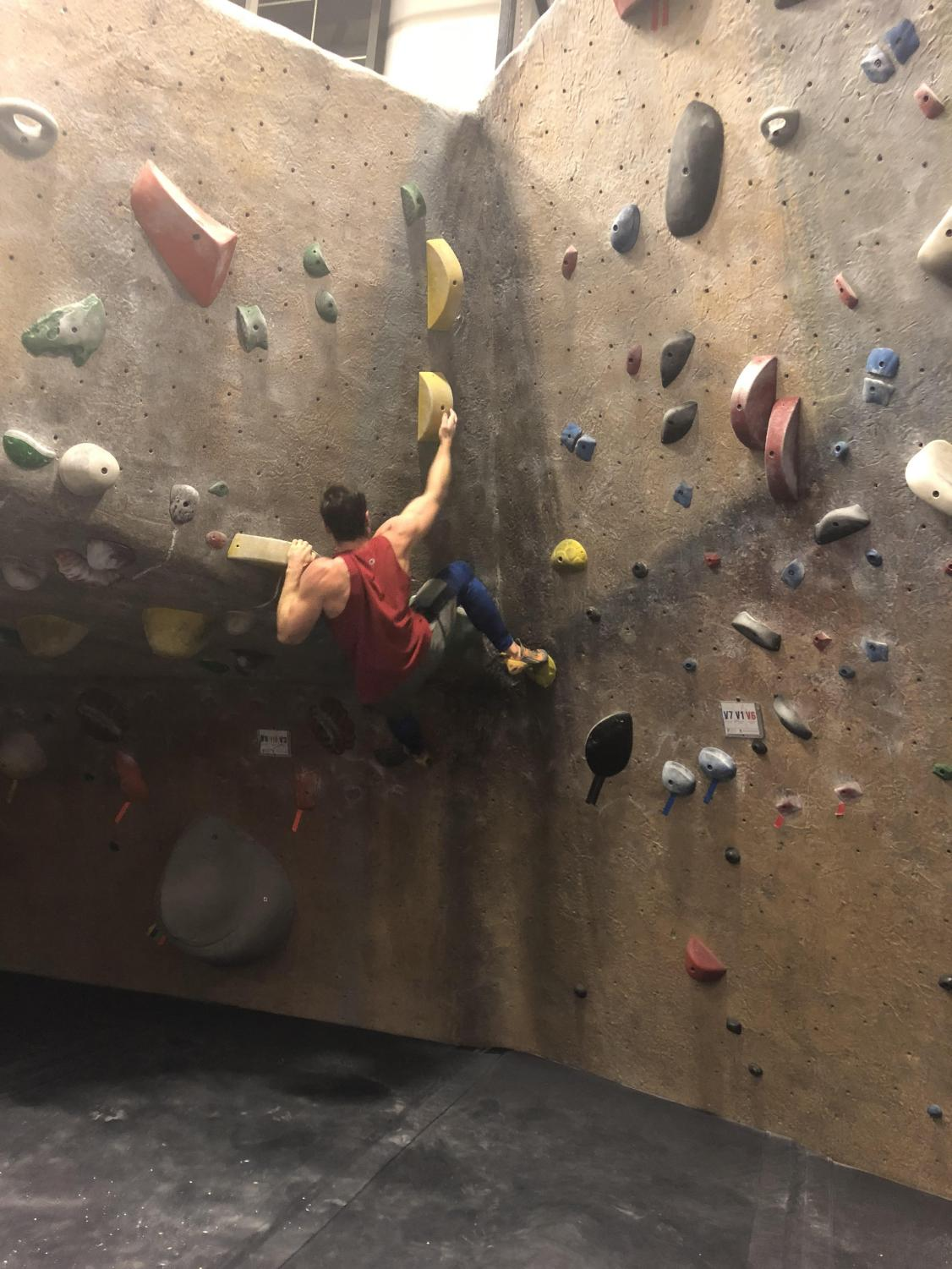 UMass sophomore Andy Dickinson scales the wall of Central Rock Gym on an outing with the Western Mass Bouldering Club.