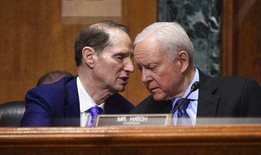 Sen. Ron Wyden, D-Ore., left, talks with committee chairman Sen. Orrin Hatch, R-Utah, right, while Treasury Secretary Steven Mnuchin testifies before the Senate Finance Committee on Capitol Hill in Washington on Feb. 14 at President Trump's fiscal year 2019 budget proposal. (Susan Walsh/AP Photo)