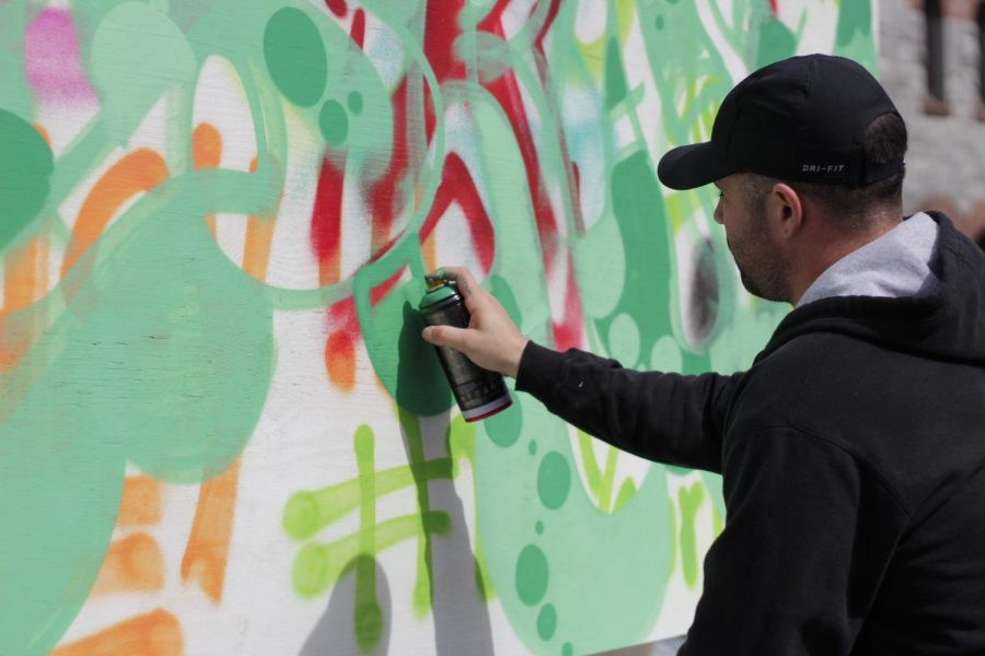 Joey+Bean%2C+who+has+been+working+as+a+graffiti+artist+for+Artists+4+Israel+for+five+years+now%2C+sprays+green+spray+paint+for+a+mural+that+will+say+%22Israel.%22+He+believes+the+ideas+being+shared+by+the+event+are+universal.+%E2%80%9CI+know+it%27s+Artists+for+Israel%2C+but+what+doesn%E2%80%99t+%5Bpeace%5D+apply+to+%E2%80%94+especially+in+this+world%2C%22+said+Bean.+%28Brian+Choquet%2F+Amherst+Wire%29