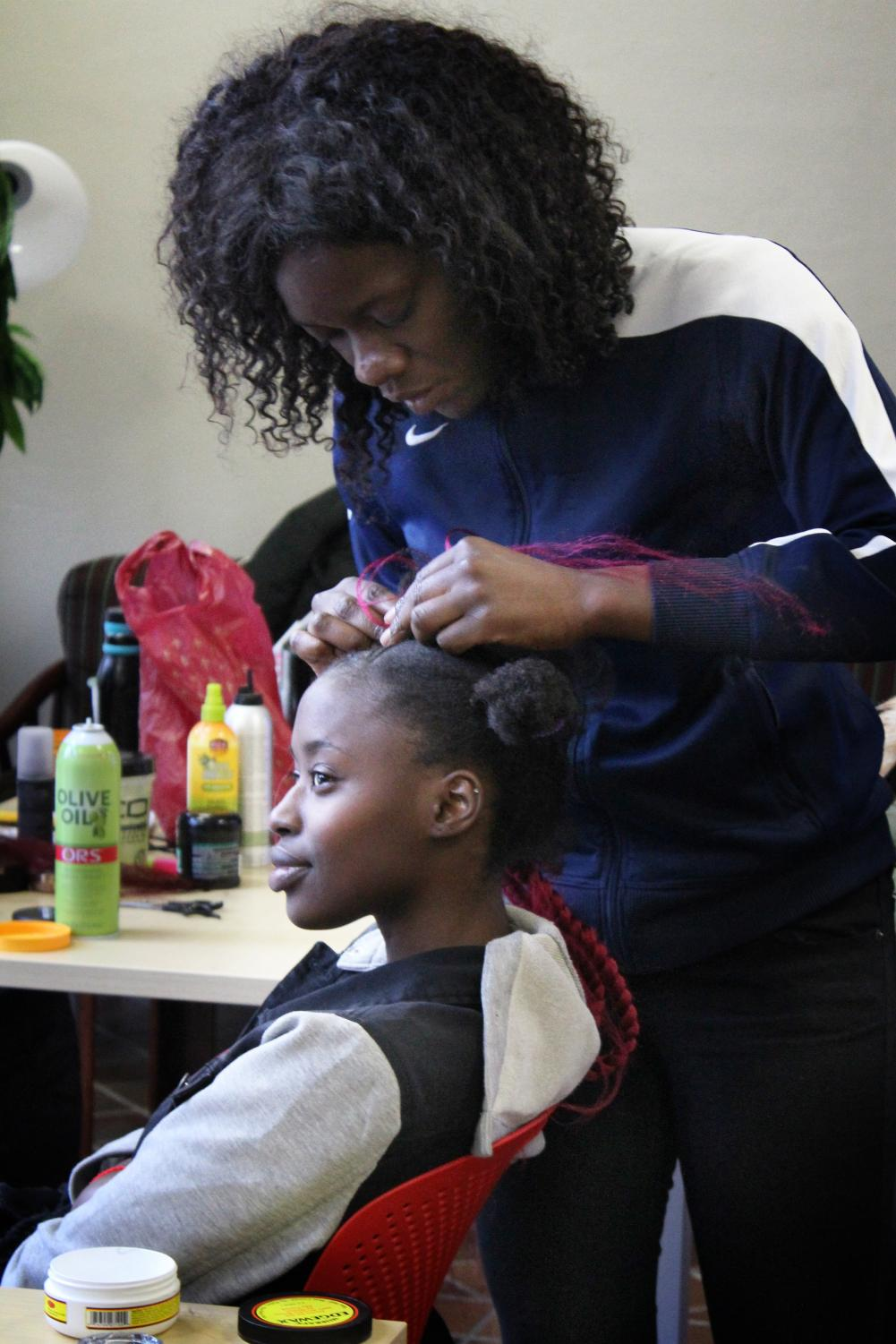 Braider Yemisi Genebar, right, works on her model, Raquel Kiddu, left, on March 23, 2018 in the Malcolm X Cultural Center located in the University of Massachusetts Amherst in Amherst, Mass. Genebar ultimately opts for a combination of techniques including