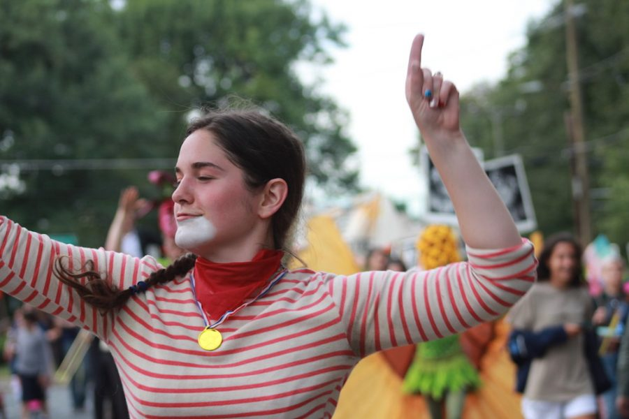 """Linda Tardif, a UMass 2011 alumna and TheatreTruck performer, dances to live music and cheering as she makes her way down North Pleasant Street toward Amherst Center. For Tardif, the event was a way for artists to shake things up. Any artists goal is to shake things up,"""" Tardiff said. """"Any good art is going to suggest something political in nature, and if we raise questions, then the art is successful.  (Maria Manning/ Amherst Wire)"""