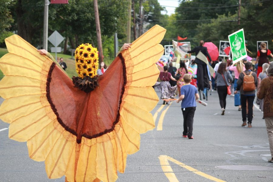 The butterfly queen flaps her wings to live music as the parade proceeds up North Pleasant Street to Amherst Center. (Maria Manning/ Amherst Wire)