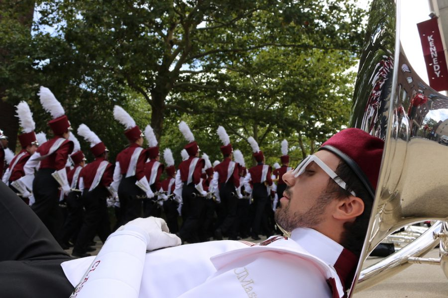 A UMass band member rests against his instrument during some down time. The Minutemen Marching Band performs a traditional march through campus to kick off the festivities for UMass Football games. (Justin Risley/ Amherst Wire)