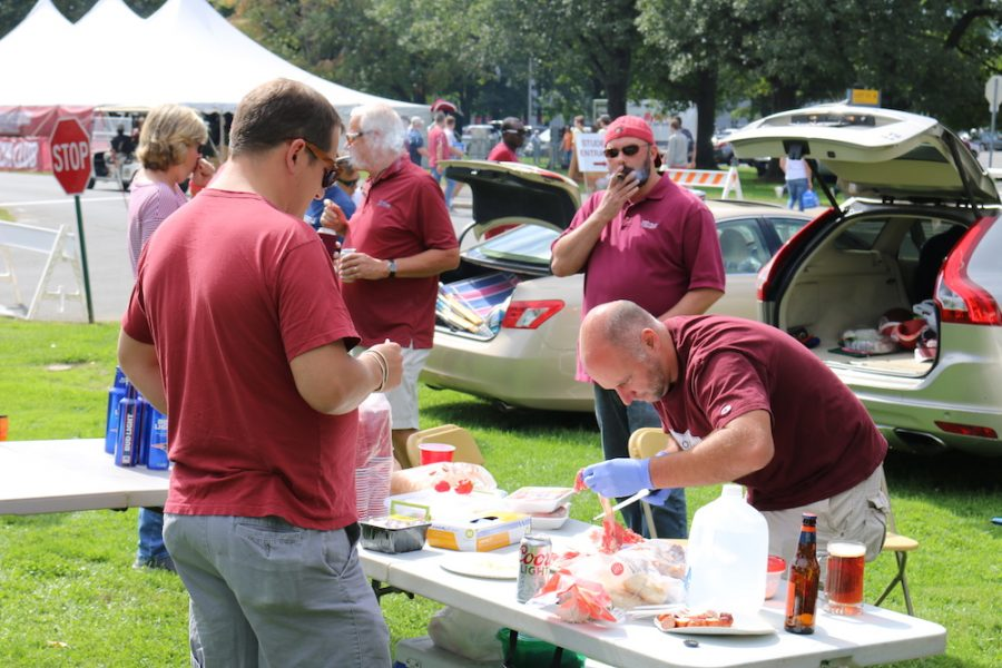 An older UMass fan prepares some meat while others watch as part of tailgating festivities that took place outside of Lot 11. (Justin Risley/ Amherst Wire)