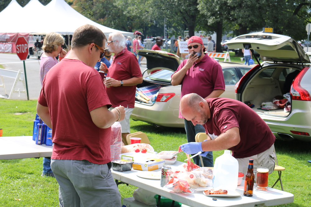 An+older+UMass+fan+prepares+some+meat+while+others+watch+as+part+of+tailgating+festivities+that+took+place+outside+of+Lot+11.+%28Justin+Risley%2F+Amherst+Wire%29