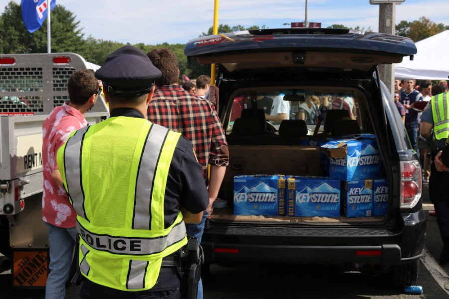 A police officer inspects a trunk full of beer in Lot 11. (Justin Risley/ Amherst Wire)