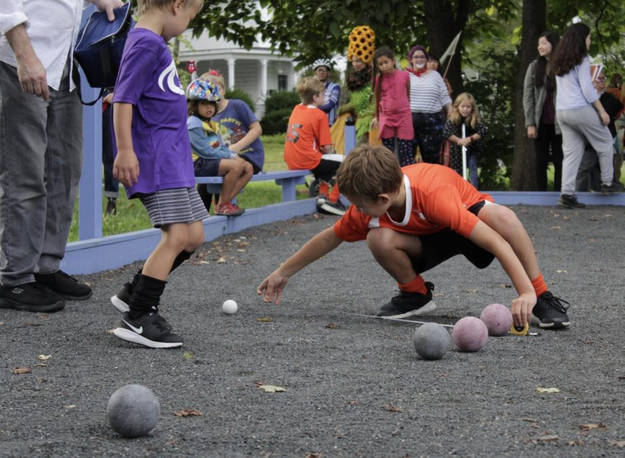 A boy measures the distance between bocce balls. The court, made by Gary Orlinsky, was one of the four attractions parade-goers could interact with when the XTCA Art Parade ended at Kendrick Park. (Brian Choquet/ Amherst Wire)