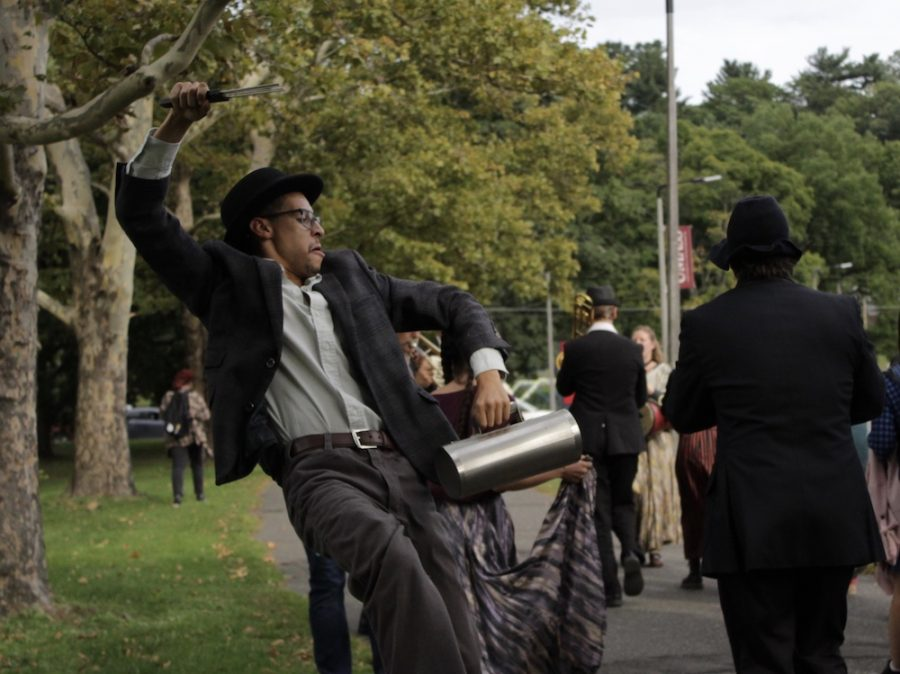 A performer hypes up the crowd, chanting and rapidly dancing while the parade makes its way up Massachusetts Avenue. (Brian Choquet/ Amherst Wire)