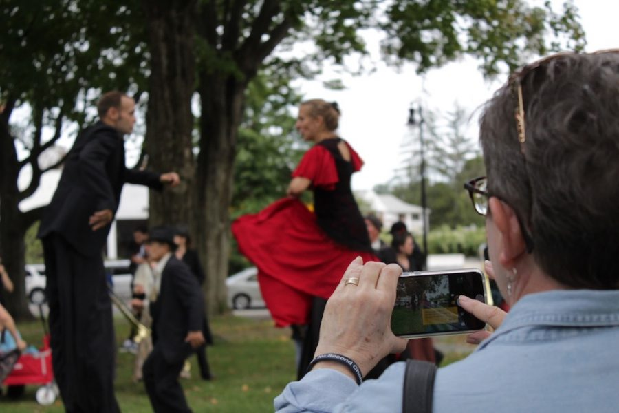 A woman attempts to take a picture of two performers as they dance on stilts. Performers and parade-goers had the chance to dance together once the parade reached Kendrick Park. (Brian Choquet/ Amherst Wire)