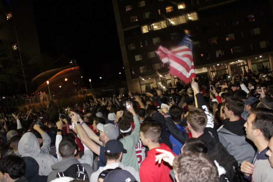 An American flag waves over the crowd of celebrators. (Brian Choquet/ Amherst Wire)