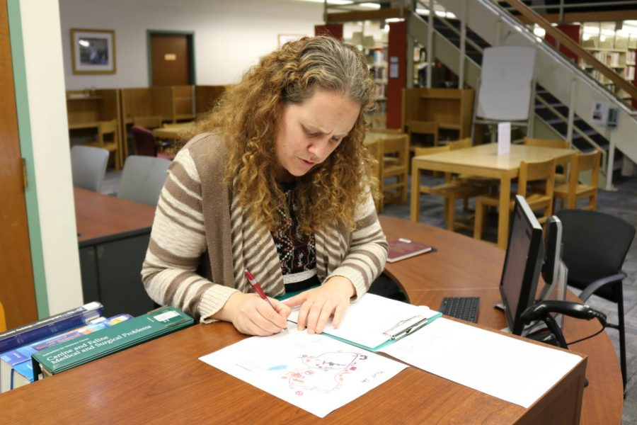 Librarian Isle Allen assists with campus directory at her desk in the Wadsworth Library. (Justin Risley/ Amherst Wire)