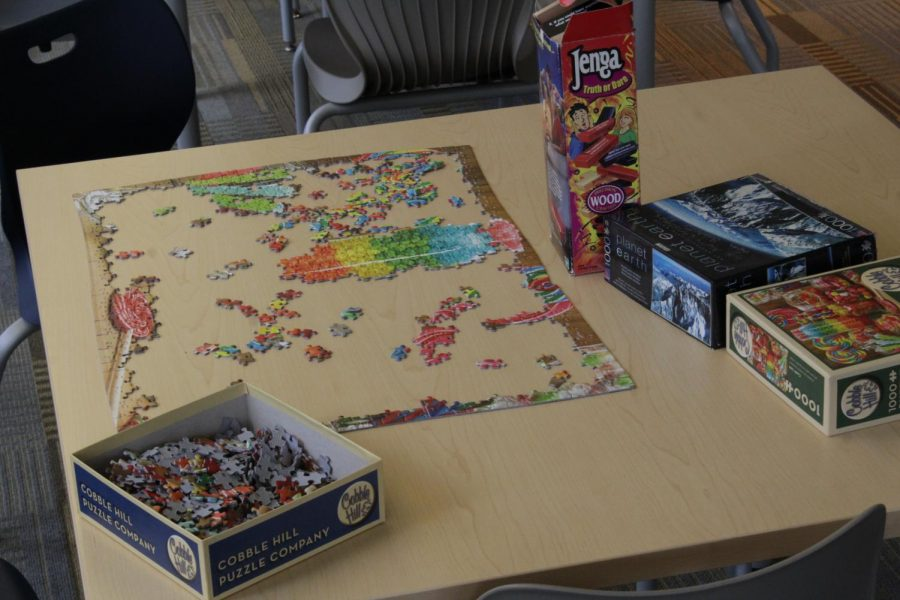 Inside New Hall, an unfinished puzzles sits on a table in an empty first floor common area.  (Brian Choquet/ Amherst Wire)