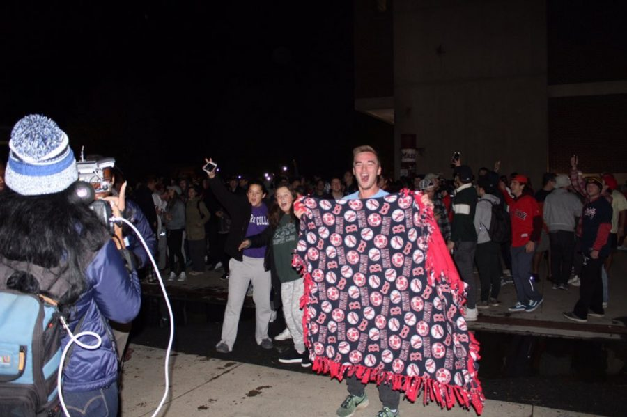 A man carries his Boston Red Sox blanket with him as he celebrates the teams victory over the Los Angeles Dodgers. (Maria Manning/ Amherst Wire)