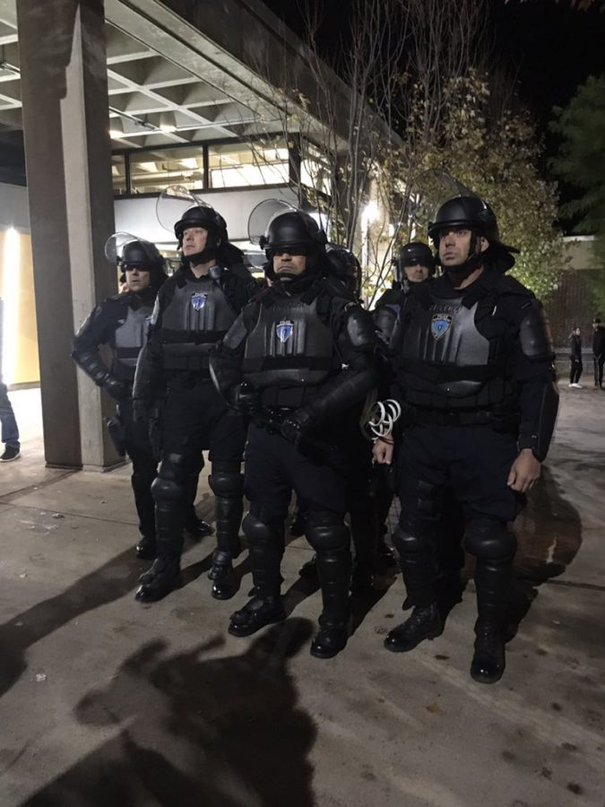 Police in riot gear stand by as students celebrate the Red Sox win. (Maria Manning/ Amherst Wire)