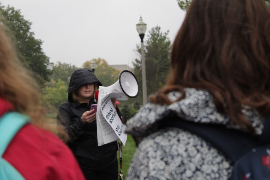UMass alumna Meghan Lemay, who graduated with a master's degree in health policy and management, reads notes off her phone as she leads the STOP Kavanaugh rally. (Brian Choquet/ Amherst Wire)