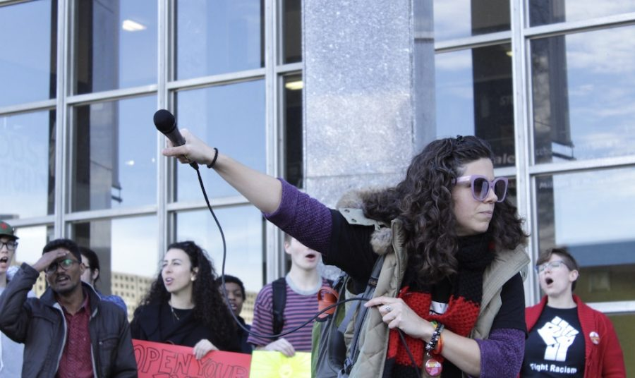 Julie Rosier, a manager of academic programs for the Labor Center at UMass, hypes up a crowd of spectators and chants,