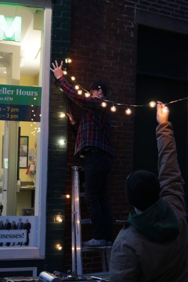 Cam MacDougall (center) begins to hang lights in Cracker Barrel Alley with the help of his classmates.(Justin Risley/ Amherst Wire)