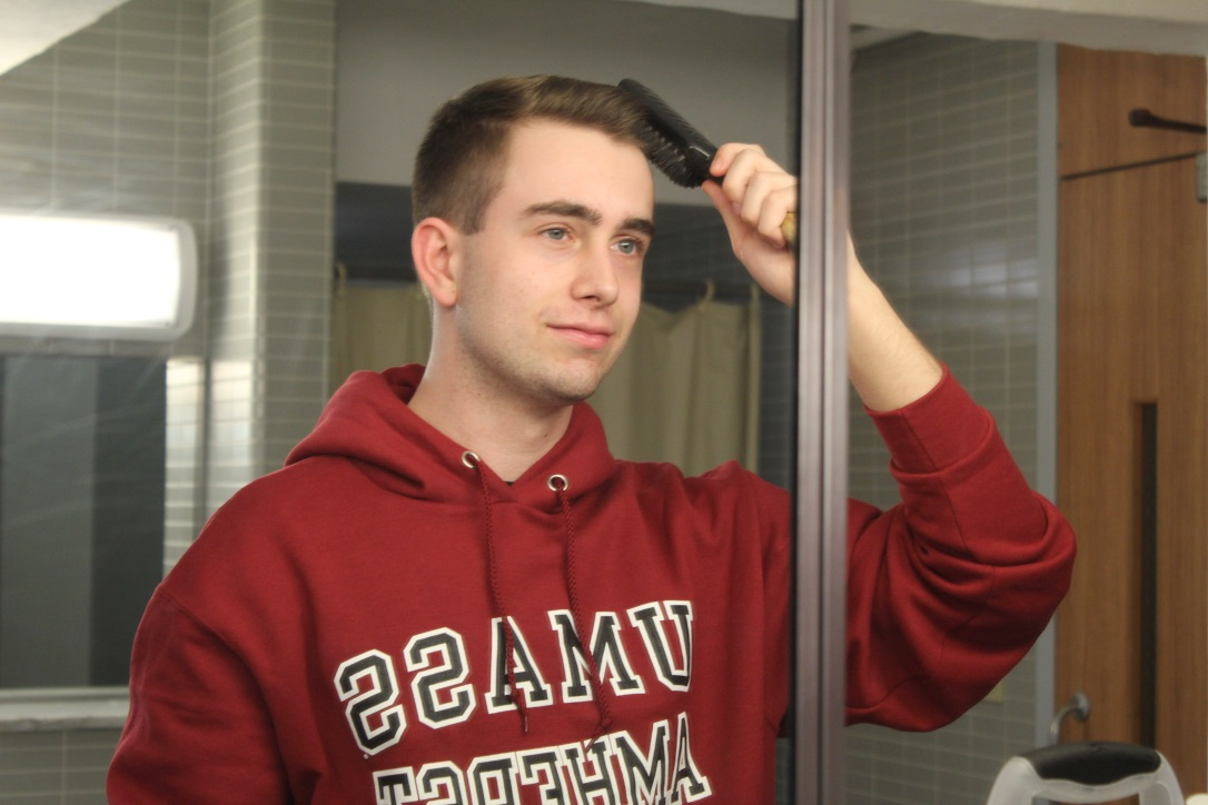 UMass Freshman Patrick Lavey takes a moment to brush his hair. (David Anderson/Amherst Wire)