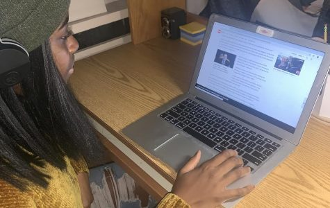 Amaka Agozino freshman political science major scrolls through online news site