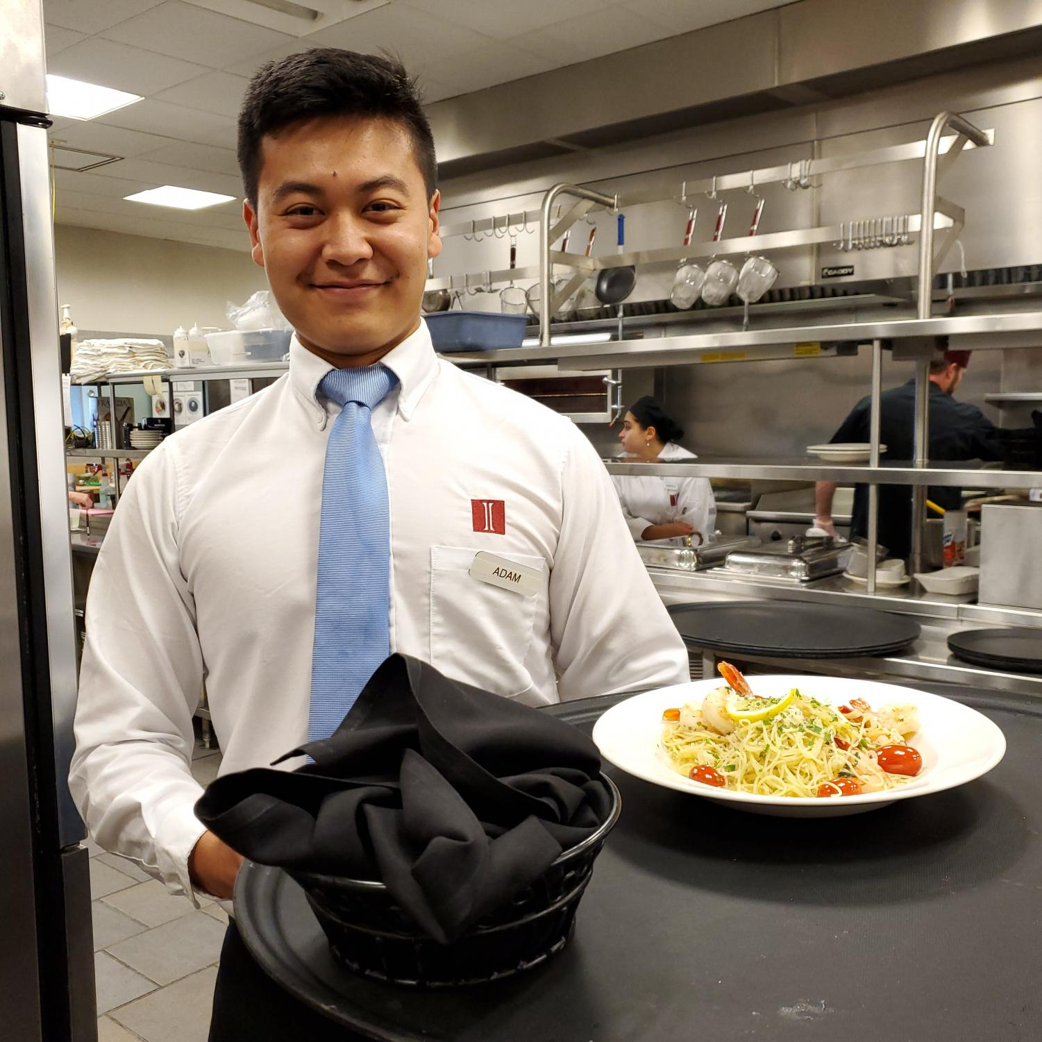Senior Adam Shi stops for a photo before serving a meal in the dining room.