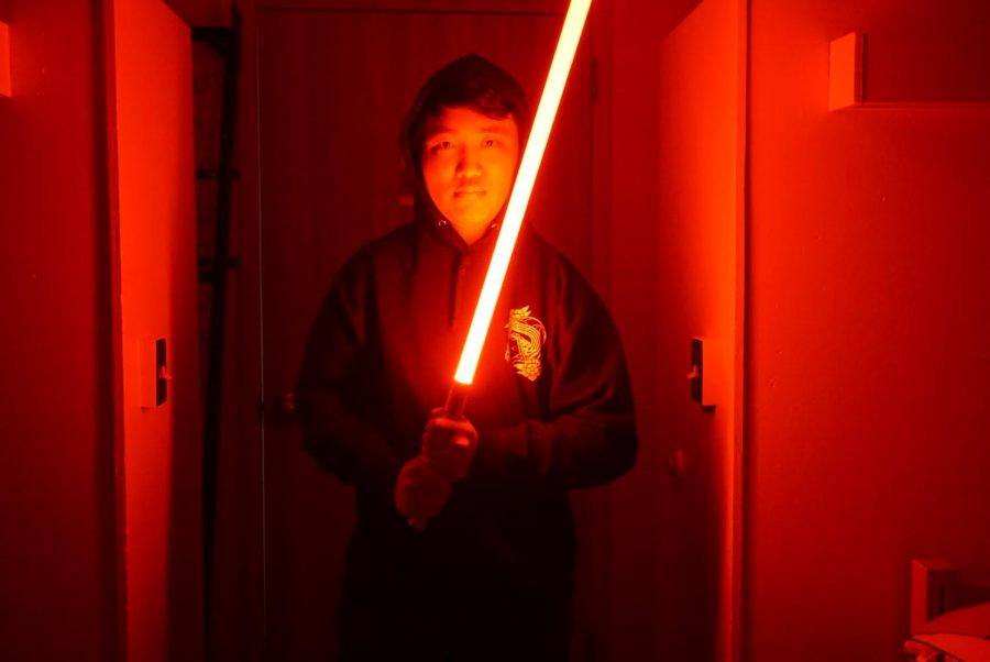 (Alex Qi poses with one of Frank Catalano's lightsabers, exchanging his PVC saber for a red, light-up blade. Photo submitted by Rebekah Panaro.)