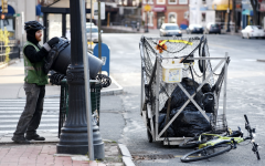 Ethan Tupelo, a member of the Pedal People, empties a trash can in downtown Northampton in April 2020.